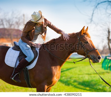 Beautiful elegance woman cowgirl nearby muzzle horse. Has smiling face, brown leather jacket and hat. Has slim body. Portrait nature. People and animals. Equestrian. Close up. American ranch.