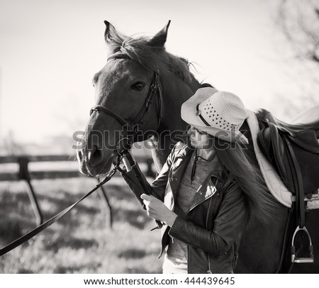 Beautiful elegance woman cowgirl nearby muzzle horse. Has smiling face, brown leather jacket and hat. Has slim body. Portrait nature. People and animals. Equestrian. Close up. Black and white