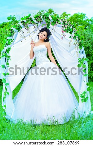 Beautiful elegant asian bride stands under the wedding arch. Wedding dress and accessories. Wedding decoration.  - stock photo