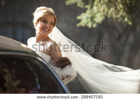beautiful elegant blonde bride smiling near old car on the background of old city - stock photo