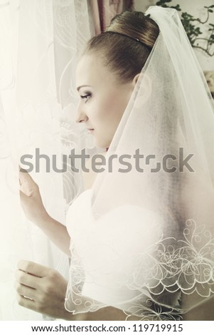 Beautiful elegant bride looks out the window - stock photo