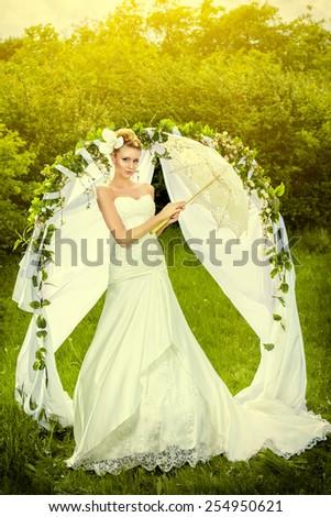 Beautiful elegant bride stands under the wedding arch. Wedding dress and accessories. Wedding decoration.  - stock photo