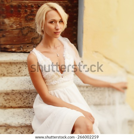 beautiful elegant bride with blond hair posing in Cannes - stock photo
