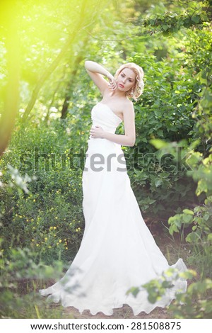 beautiful elegant bride with blond hair posing in the green forest - stock photo