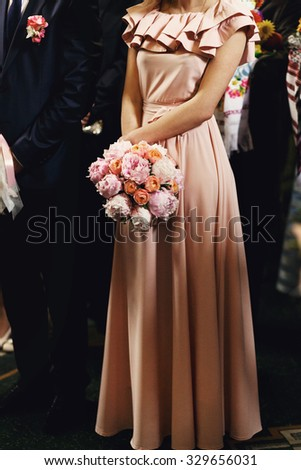 Beautiful elegant bridesmaid in pink dress holding a rose bouquet in church at wedding ceremony - stock photo