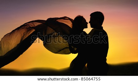 Beautiful elegant couple in love dancing at sunset.