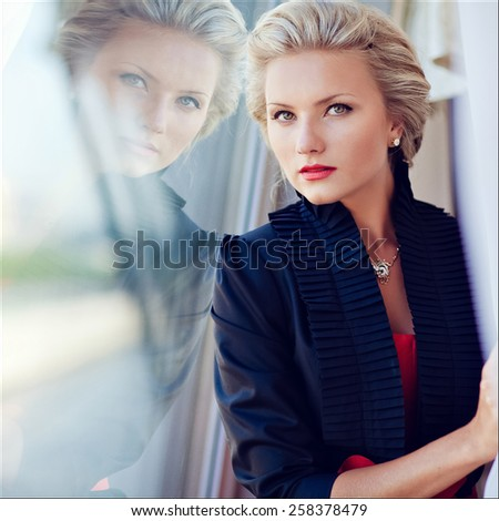 Beautiful elegant exquisite blonde girl looks straight and strictly, reflected in the glass