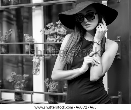 Beautiful elegant lady in hat and little black dress outside.