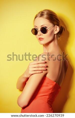 Beautiful elegant lady over bright yellow background. Beauty, fashion concept. Optics. - stock photo