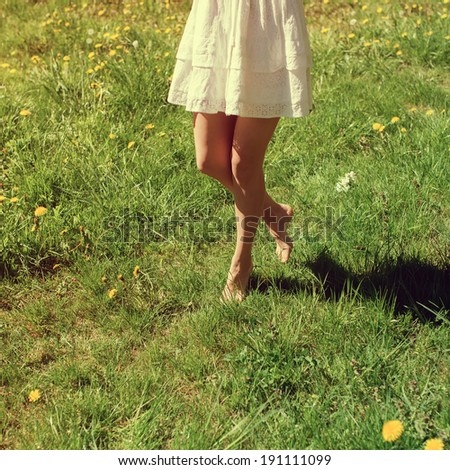 Beautiful elegant legs on the green grass on a sunny day - stock photo