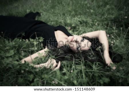 beautiful elegant mature woman lie in grass - stock photo