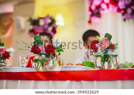 Beautiful elegant wedding reception table arrangement, red flowers - stock photo