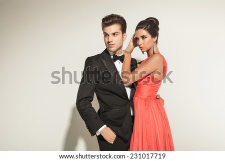 Beautiful elegant woman fixing her hair while her lover is looking away with one hand in his pocket. - stock photo