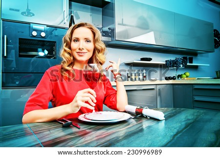 Beautiful elegant woman having a dinner at a kitchen at home. Home interior. - stock photo