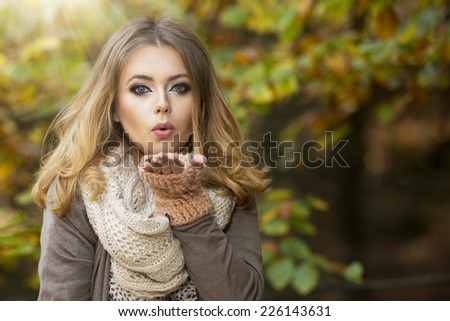 Beautiful elegant woman  in a park in autumn send kiss - stock photo