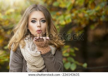 Beautiful elegant woman  in a park in autumn send kiss - stock photo