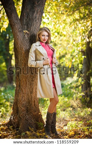 Beautiful elegant woman in autumn park .Young pretty woman at the autumn park. Beautiful woman spending time in park during autumn season .Young pretty woman at the autumn park