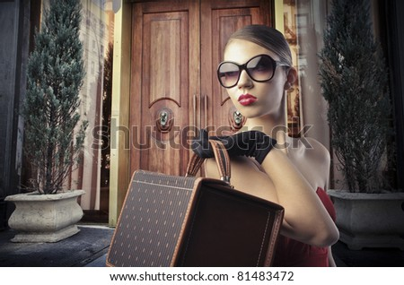 Beautiful elegant woman in front of the entrance door of a luxury building - stock photo