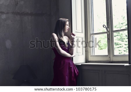 Beautiful elegant woman looking out of a window