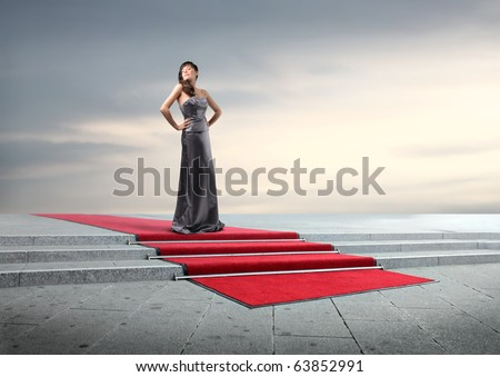 Beautiful elegant woman on a red carpet - stock photo