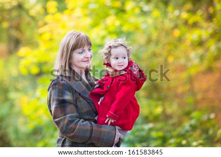 Beautiful elegant woman playing with a little toddler girl in a red jacket in a autumn park with colorful yellow trees