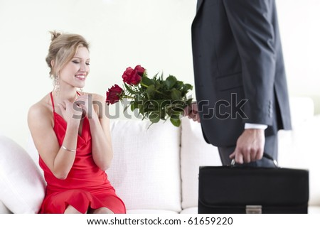 Beautiful elegant woman receiving red roses on Valentine's Day, Birthday or Anniversary - stock photo