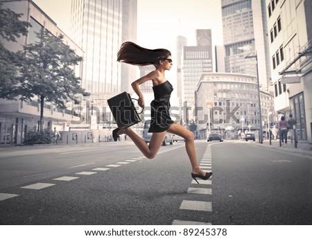 Beautiful elegant woman running on a city street - stock photo