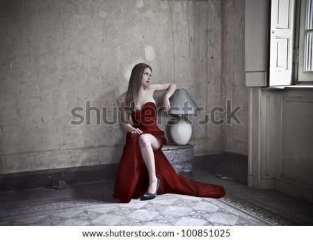 Beautiful elegant woman sitting in an old room - stock photo