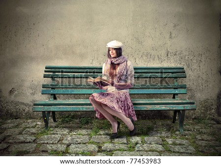 Beautiful elegant woman sitting on a park bench and reading a book - stock photo