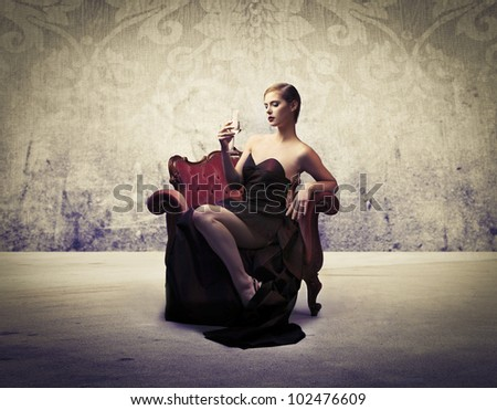 Beautiful elegant woman sitting on an armchair and having a glass of wine - stock photo