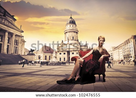 Beautiful elegant woman sitting on an armchair on a town square
