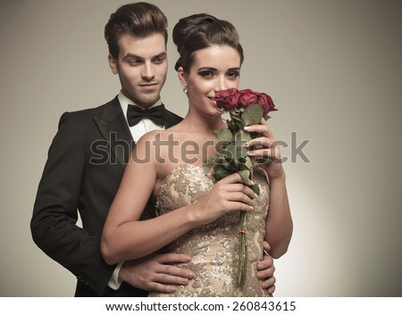 Beautiful elegant woman smelling a bunch of red roses while her husband is embracing her from the back. - stock photo