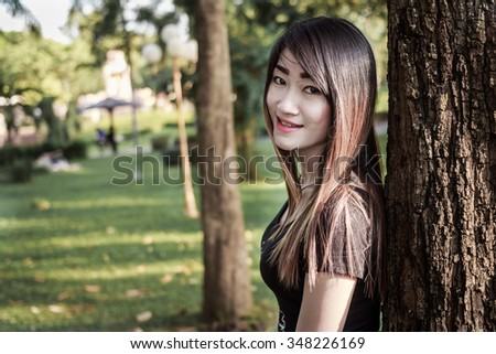 Beautiful elegant woman standing in a park in autumn black and white