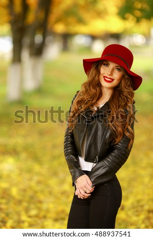 Beautiful elegant woman standing in fashionable red Hat in a park in autumn