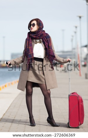 Beautiful elegant woman waiting for ship in the harbor - stock photo
