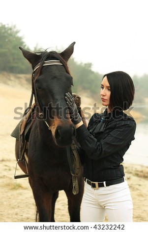 Beautiful elegant woman with a horse near the river - stock photo
