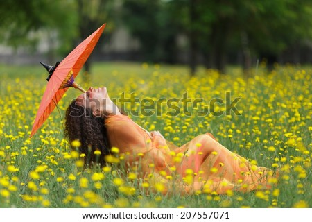 Beautiful elegant woman with an orange parasol draped in a matching chiffon scarf tilting back her head with a smile of bliss as she walks through a meadow filled with colorful yellow summer flowers - stock photo