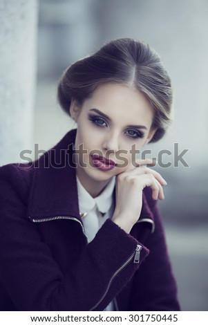 beautiful elegant woman with bright makeup wearing a warm jacket in the street - stock photo