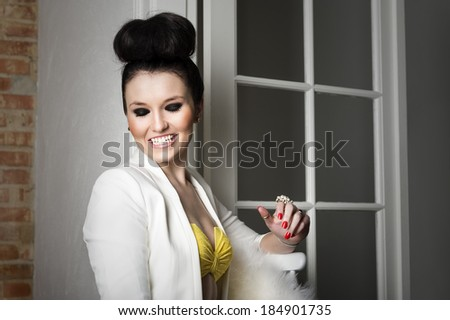 Beautiful elegant woman with her hair in a bun wearing a stylish jacket flirting and laughing as she sits on a chair indoors - stock photo