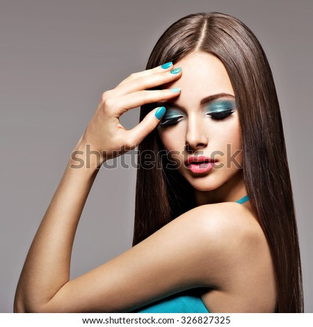 Beautiful elegant woman with turquoise make-up and nails - pose at studio