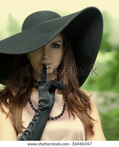 Beautiful elegant young lady enjoying a day in the park - stock photo
