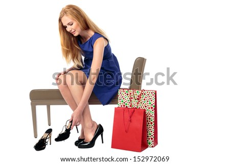 Beautiful elegant young woman choosing a new pair of shoes sitting on a seat in a store trying on a stylish pair of stilettos, isolated on white