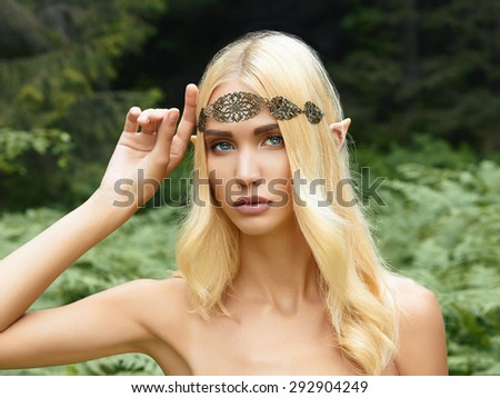 beautiful elf girl. fantasy young woman in woods - stock photo
