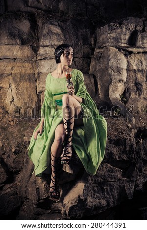 Beautiful elf princess is drinking a wine on the rock. - stock photo