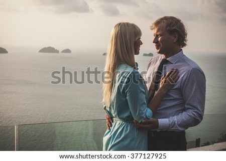 Beautiful embracing couple dressed in formal wear on the tropical ocean background. - stock photo