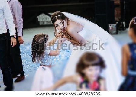 Beautiful emotional bride celebrating with children at wedding reception - stock photo