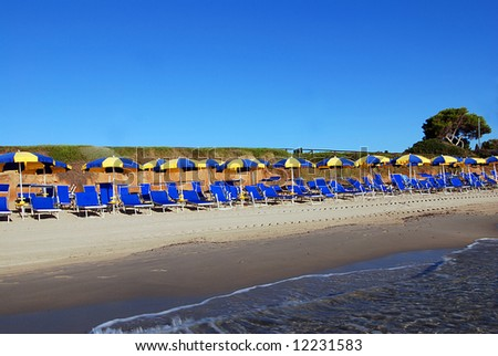 Beautiful empty beach wit umbrellas, sea and a blue sky - stock photo