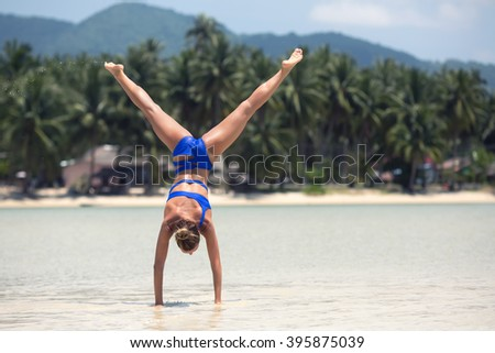 stock photo beautiful energetic young woman doing handstand on the beach 395875039