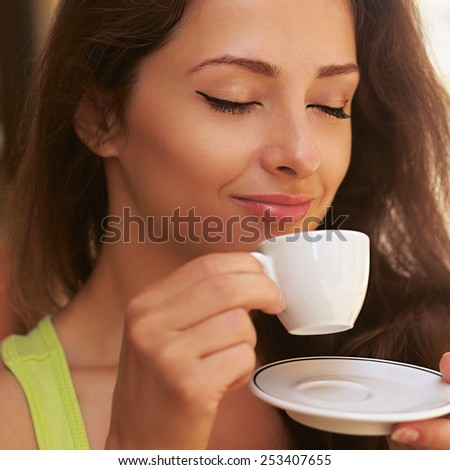 Beautiful enjoying woman drinking coffee from cup outdoors with closed happy eyes - stock photo