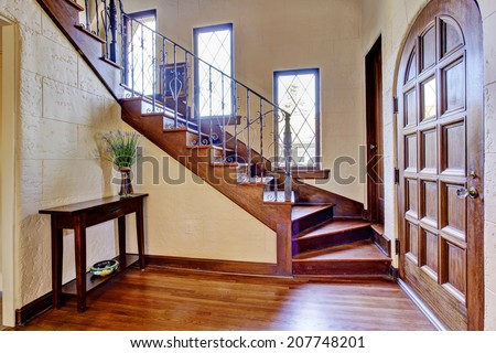 Beautiful entrance hallway in luxury house with wooden entrance door and staircase with iron railings - stock photo
